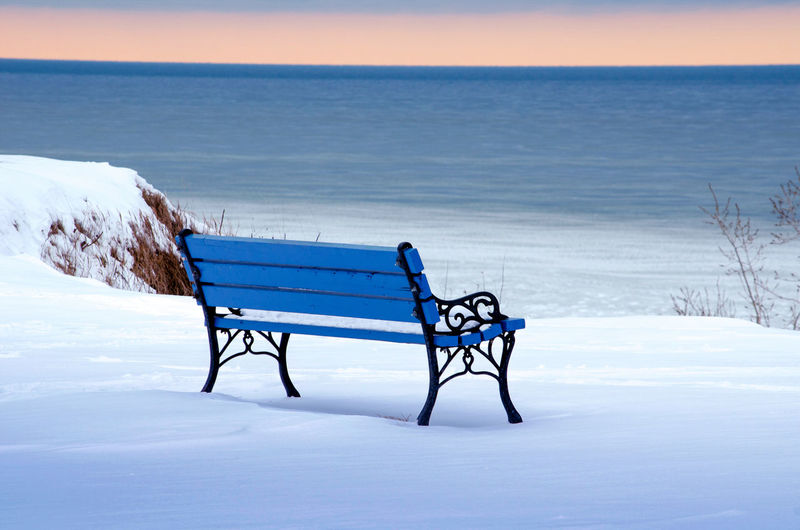 Empty Bench On Snow Covered Land By Sea Against Sky