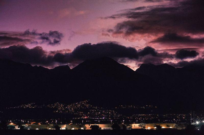 Silhouette of illuminated mountain against dramatic sky