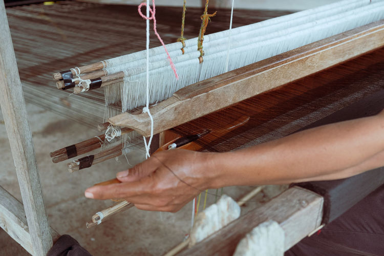 Cropped hand waving textile on loom in factory