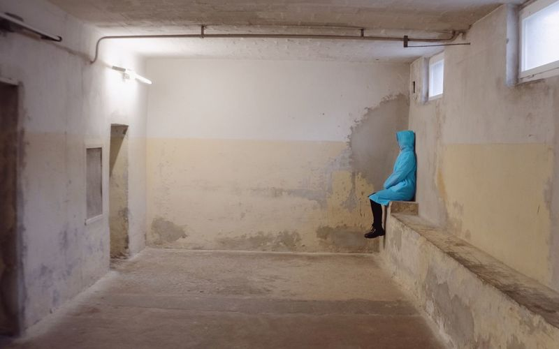 Side View Of Person With Blue Hooded Shirt Sitting In Empty Room