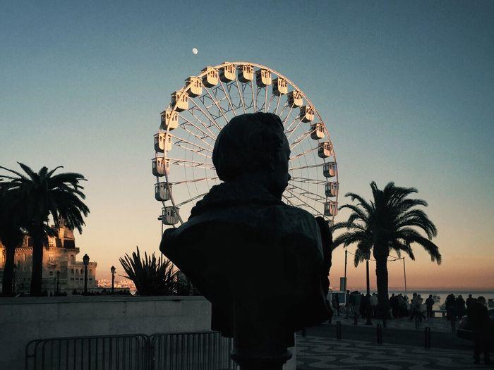 Bust against ferris wheel during sunset