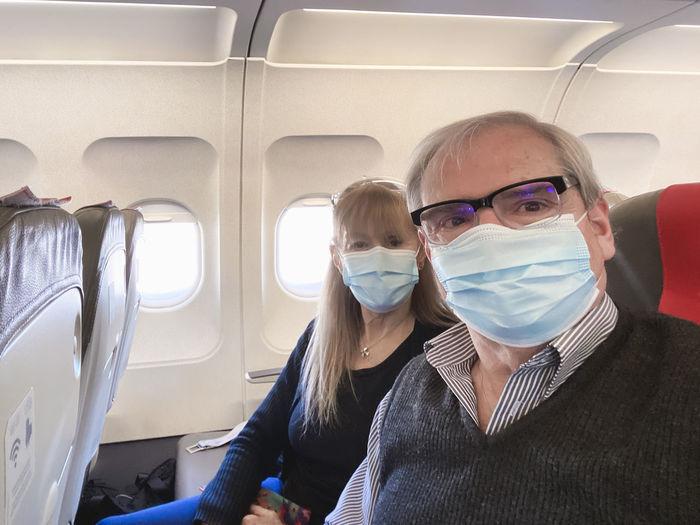 Portrait of senior couple wearing mask sitting at airplane