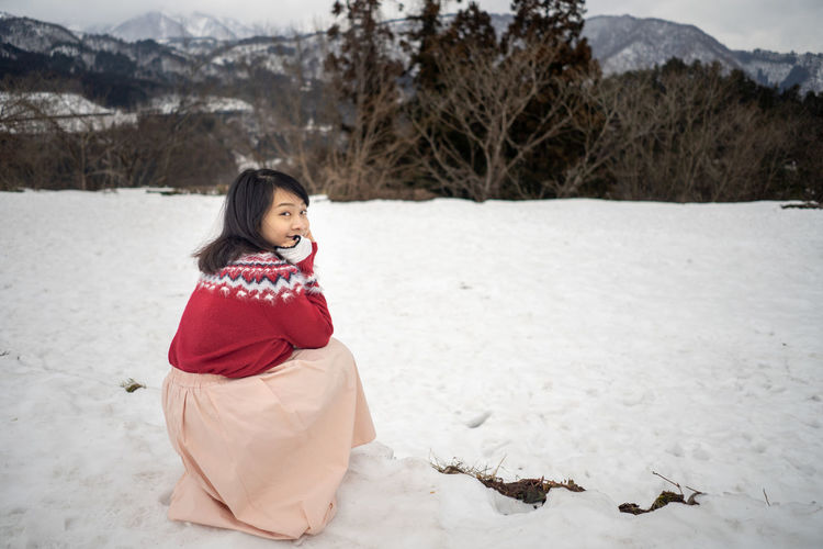 Portrait of woman crouching on snow covered land