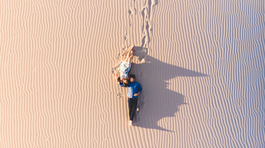 High Angle View Of Couple Lying On Sand At Desert