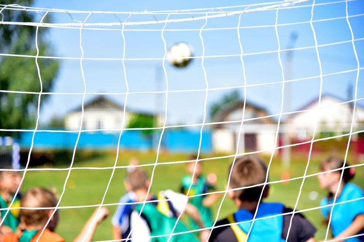Children Playing Soccer On Field Seen Through Net