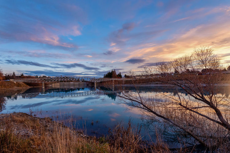 The Bridge at Lake Tekapo Beauty In Nature Bridge Cloud - Sky Environment Lake Lake Tekapo Nature No People Non-urban Scene Outdoors Plant Reflection Scenics - Nature Sky Sunset Tranquil Scene Tranquility Tree Water