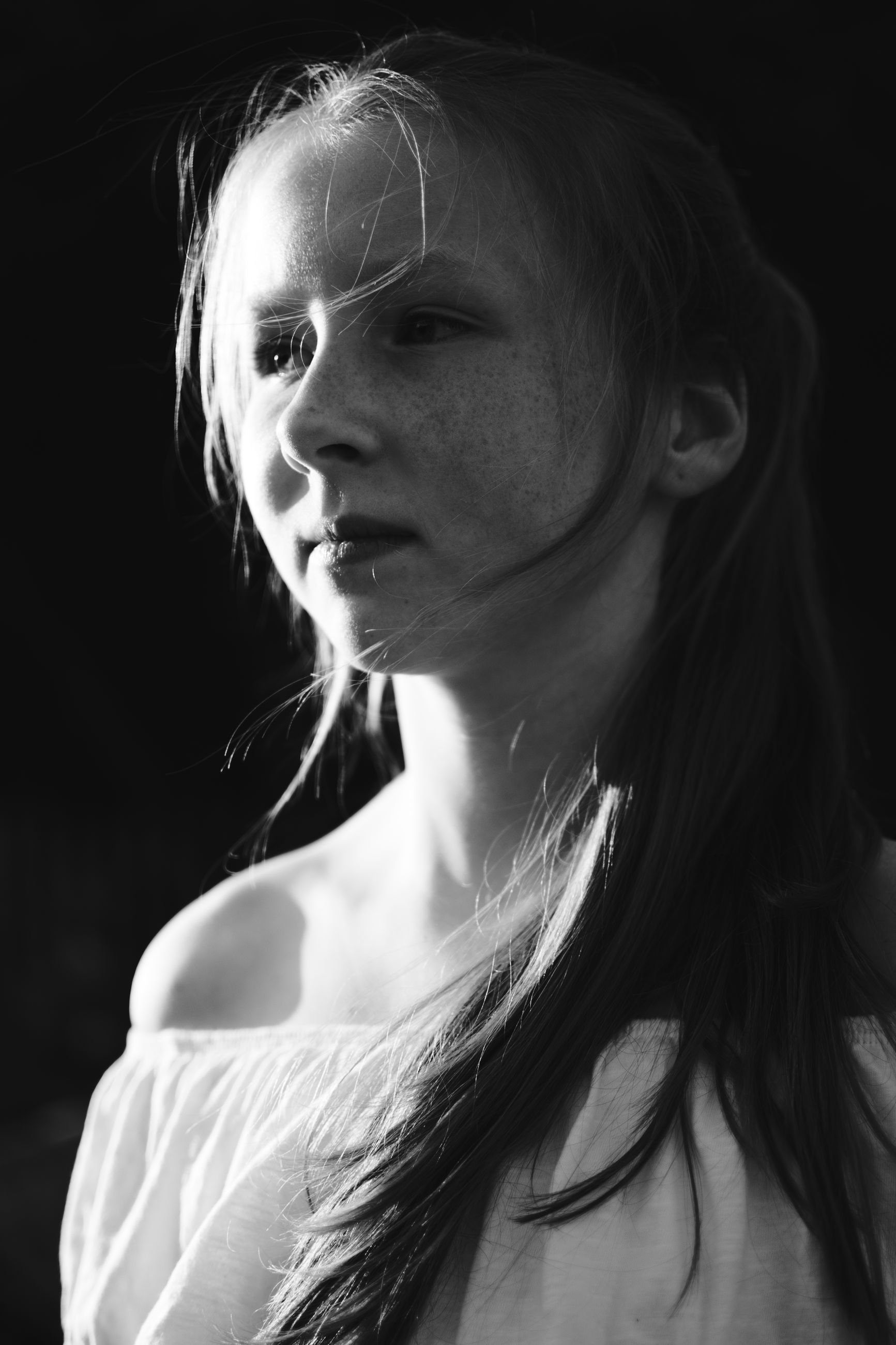 one person, headshot, young adult, lifestyles, young women, long hair, portrait, hair, close-up, women, hairstyle, real people, looking, looking away, leisure activity, black background, focus on foreground, adult, contemplation, teenager, beautiful woman