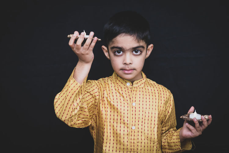 Portrait of boy holding candles standing against black background