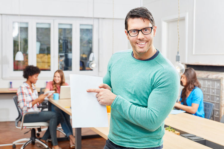 Cheerful businessman looking at documents while colleagues sitting at background in office
