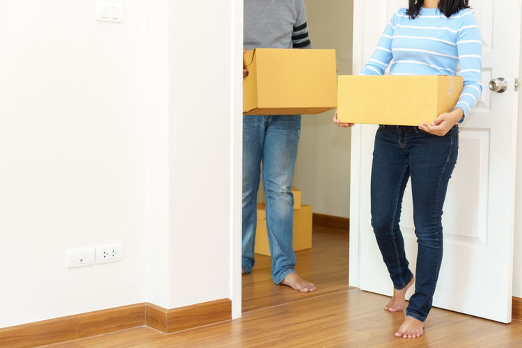 Low section of couple holding boxes while standing on hardwood floor at home