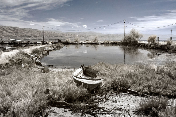 A boat rotting on land at the small harbour of Kopraina, in western Greece. The decay of the harbour is denoted though the decay of the boat Infrared Abstract Boat Day Grass Greece Nature Nautical Vessel No People Outdoors Sky Tree Water