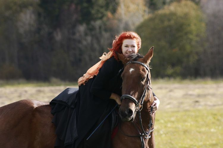 Portrait of young woman riding horse on field
