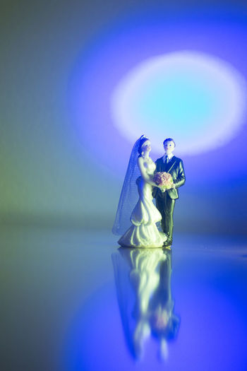 Close-up of figurine on table against blue background