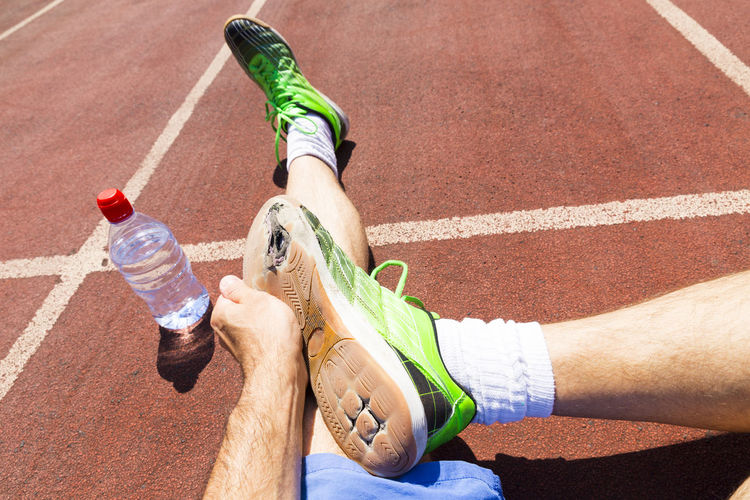 Low section of athlete with torn shoes sitting on track