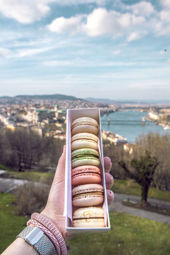 Close-up of hand holding macaroons in box against sky