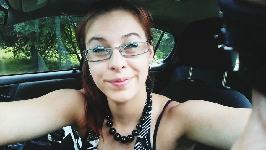 Portrait Of Young Woman Wearing Eyeglasses In Car