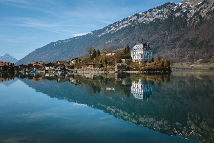 Check out my prints at https://simonmigaj.com/shop/ and visit my IG http://www.instagram.com/simonmigaj for more inspirational photography from around the world. Mountain Reflection Water Built Structure Architecture Sky Building Exterior Waterfront Building Mountain Range Nature Scenics - Nature Beauty In Nature Lake No People Day Tranquility Tranquil Scene Outdoors Switzerland Iseltwald Palace Castle Cloud - Sky