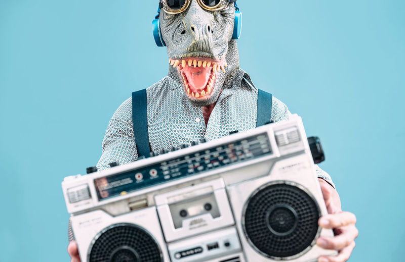 Midsection of man wearing mask while holding radio while standing against blue background