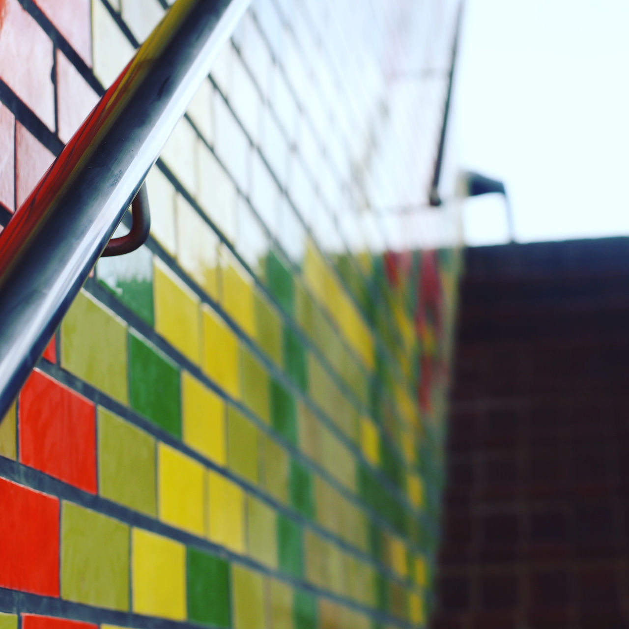 LOW ANGLE VIEW OF METAL FENCE AGAINST MULTI COLORED WALL
