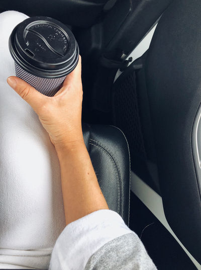 Midsection of person holding take out coffee cup in car