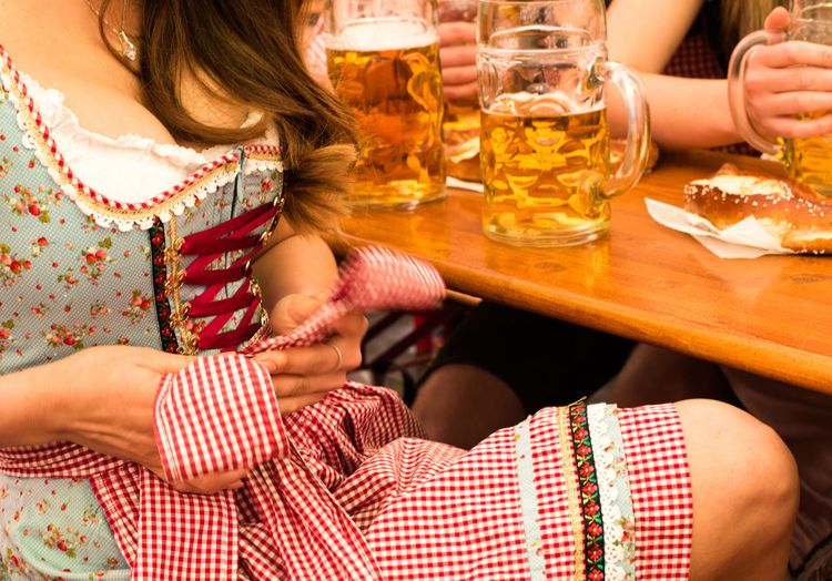 Midsection of woman adjusting dirndl by table at restaurant