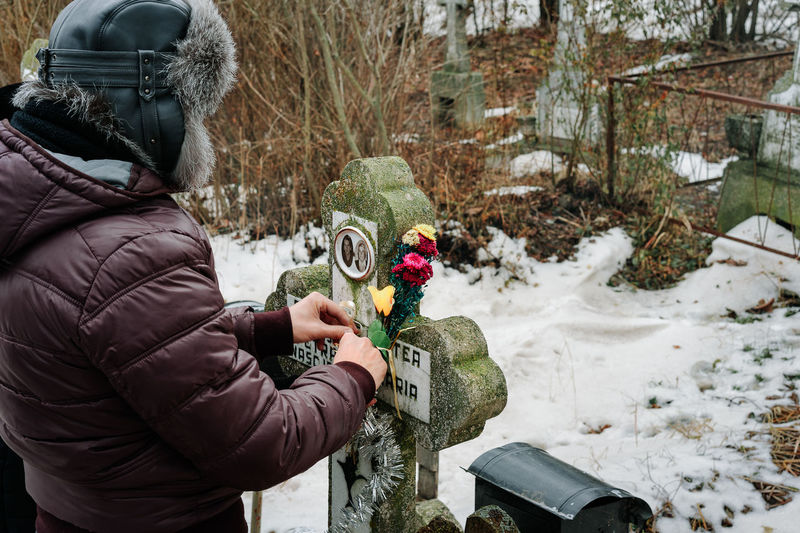 Man touching tombstone during winter