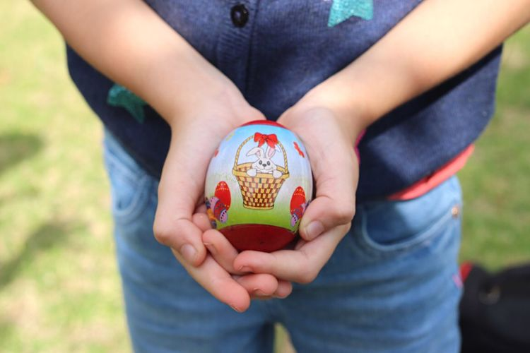 Midsection of girl holding easter egg