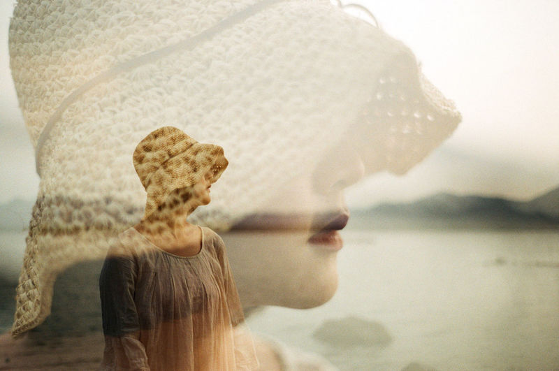 Double exposure of woman at lakeshore