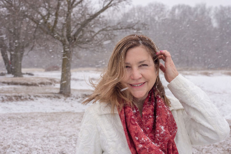Portrait of smiling woman during snowfall
