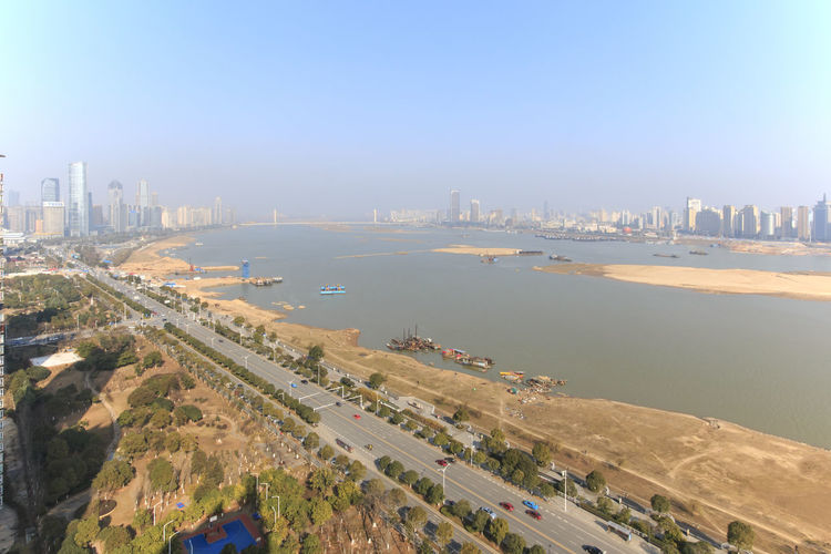High Angle View Of Road In City By River Against Sky