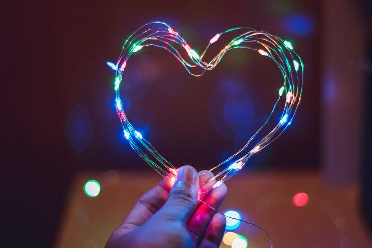 Close-up of hand holding illuminated string light