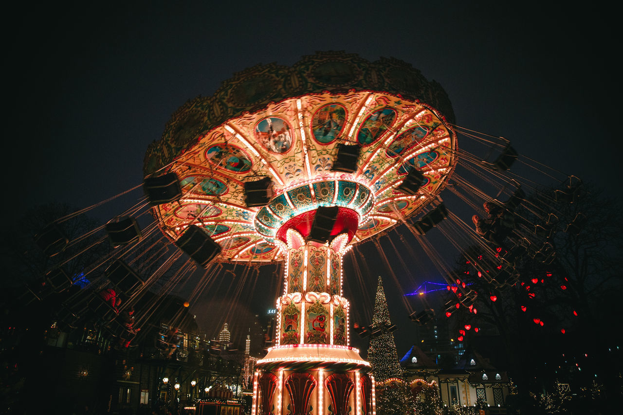 Illuminated chain swing ride spinning at night