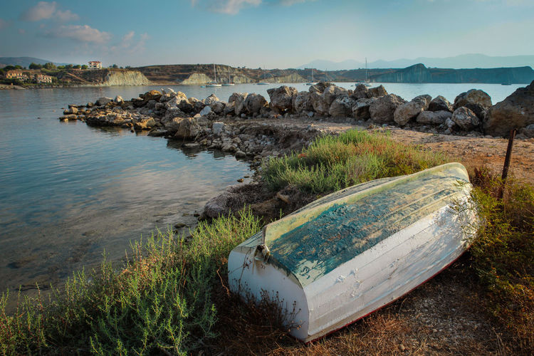 Small upside-down boat pulled on a shore Water Sky Nature Tranquility Tranquil Scene Scenics - Nature No People Beauty In Nature Land Beach Nautical Vessel Rock Grass Cloud - Sky Sea Transportation Abandoned Rowboat Boat Worn Out Seashore Bay Upside Down