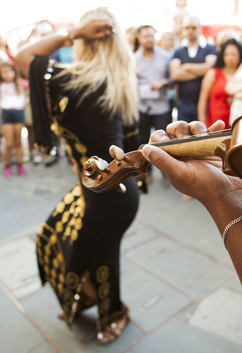 Cropped Hand Playing Musical Equipment With Street Performer Dancing