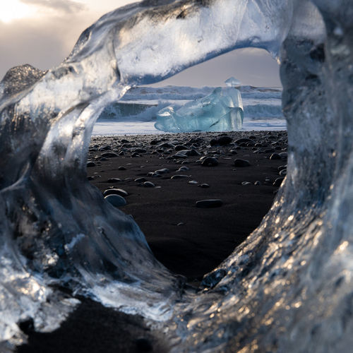 Sea seen through hole in ice at beach during winter
