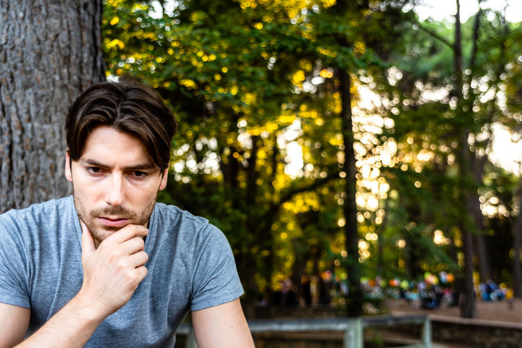 Thoughtful man looking away while sitting by tree trunk