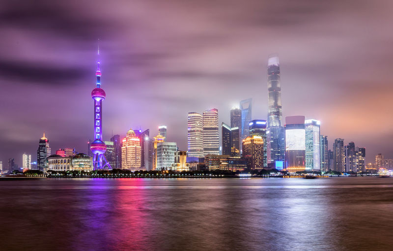 The illuminated skyline of Shanghai on a cloudy night, China Lights Modern Shanghai Shanghai, China Tourist Attraction  Travel Architecture Building Building Exterior China City Cityscape Illuminated Modern Night Pudong Purple Sky Skyscraper Tall - High Tower Travel Destinations Urban Skyline Water Waterfront