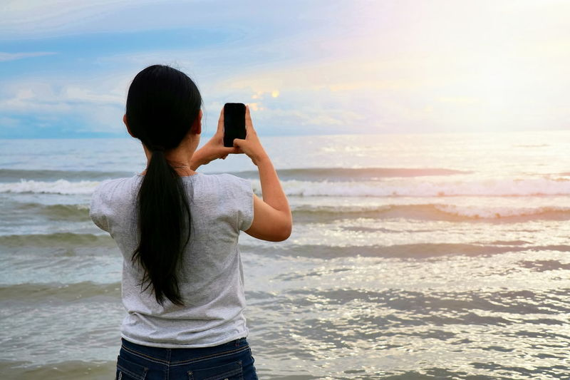 Woman photographing at beach against sky