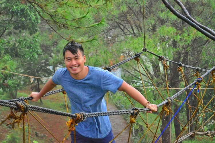 Portrait Of Smiling Young Man Standing On Rope Bridge Against Trees In Forest
