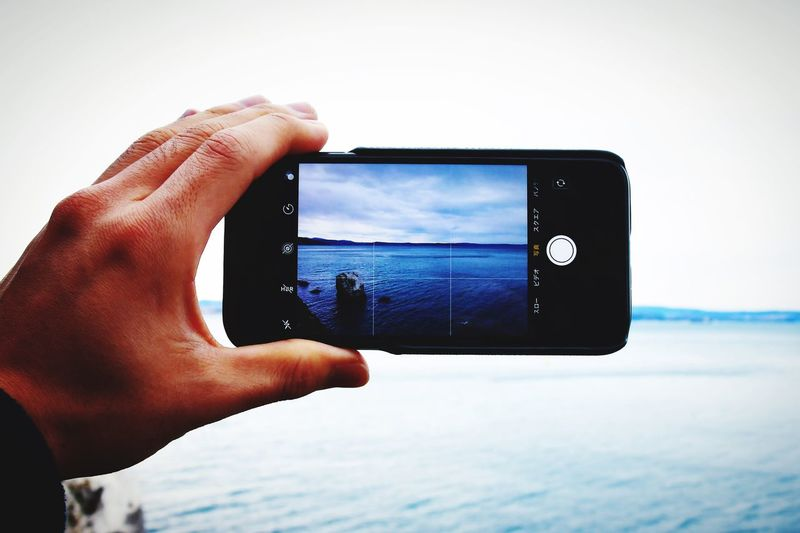 Cropped hand photographing sea from mobile phone