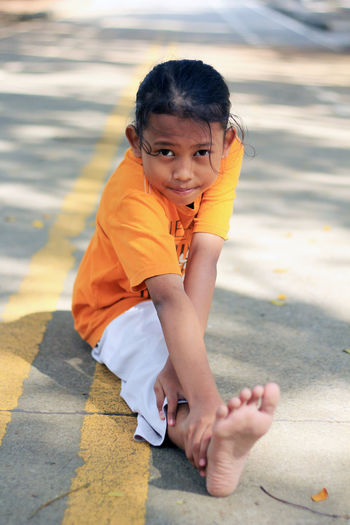 Portrait Of Girl Doing Splits On Road