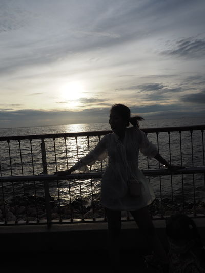 Rear view of woman standing by railing against sky during sunset