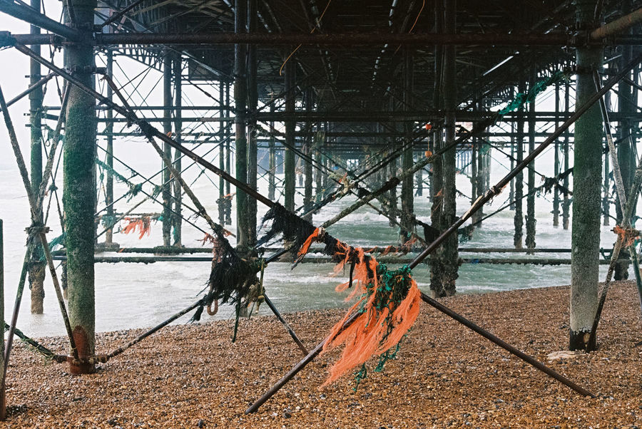 Scraps of plastic and other jetsam stuck to the metal beams of the structure beneath the Brighton Pier boardwalk fluttering in the wind 35mm Film Analogue Photography Brighton Pier Construction Film Pier Architecture Beach Boardwalk Built Structure England Film Photography Girder Metal No People Scraps Sea Seafront Seascapes Structure Tatters Uk Water Wind Windy