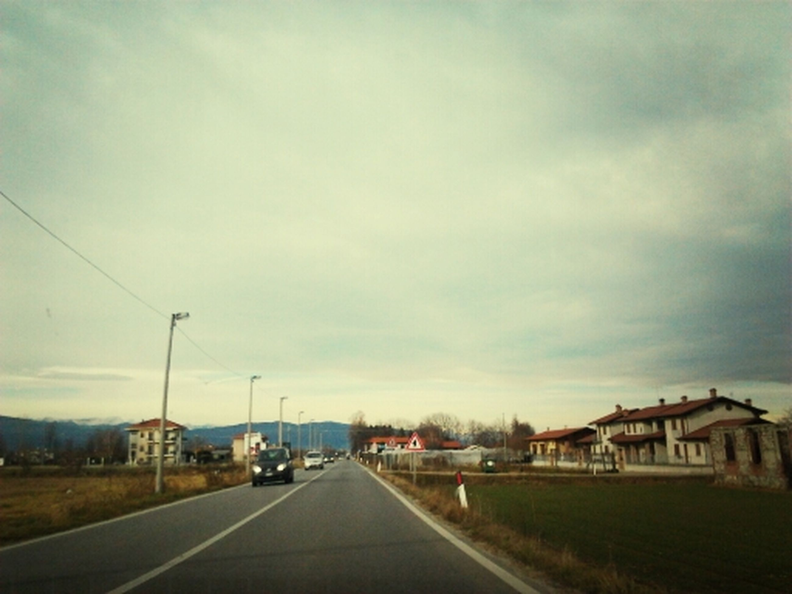 the way forward, transportation, sky, road, diminishing perspective, vanishing point, cloud - sky, cloudy, road marking, built structure, architecture, building exterior, empty, street, cloud, empty road, long, overcast, outdoors, country road