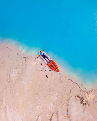 High angle view of man with arms outstretched lying on boat at beach