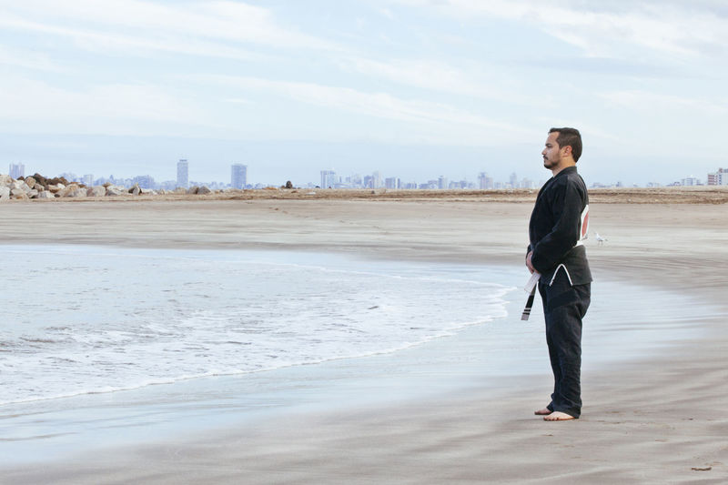 Side view of man standing on beach against sky