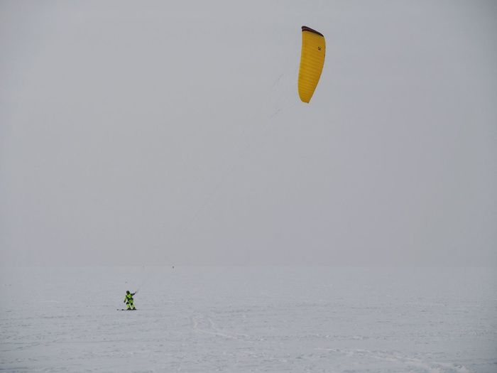People paragliding in sea against sky