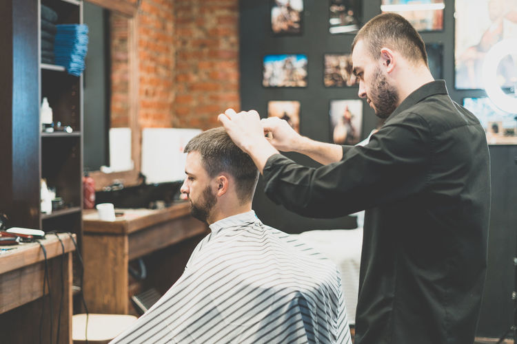 Side view of barber cutting customer hair