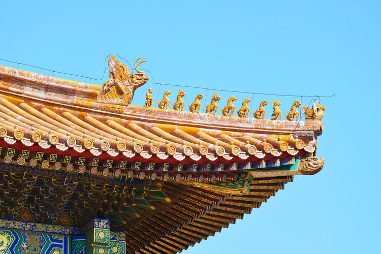 Strung wooden puppet on a roof Asian  Beijing Peking  Puppets Roof Tradition Animal Representation Architecture Blue Built Structure Chinese Chinese Dragon Clear Sky Colorful Detailed Detailed To Perfection Dragon Handmade Hidden Palace History Low Angle View No People Roof Sky Travel Destinations