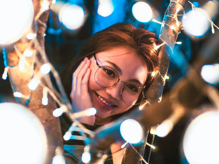 light it up Portrait Illuminated Headshot Glasses One Person Smiling Eyeglasses  Happiness Leisure Activity Lifestyles Front View Looking At Camera Young Women Young Adult Emotion Real People Women Lighting Equipment Glowing Christmas Lights Hairstyle Lens Flare Beautiful Woman